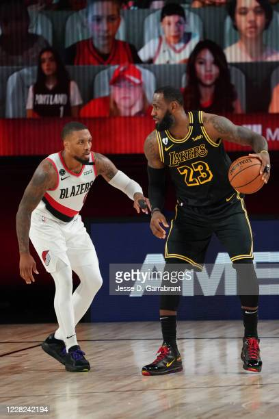 LeBron James of the Los Angeles Lakers handles the ball against Damian Lillard of the Portland Trail Blazers during Round One Game Four of the NBA...