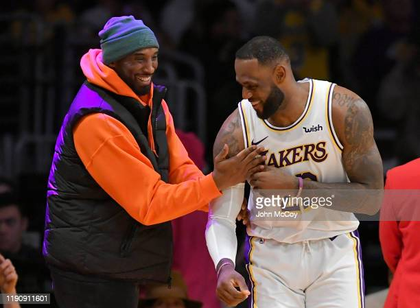 LeBron James of the Los Angeles Lakers has a moment on the sideline with former Laker Kobe Bryant in the second half during a game against the Dallas...