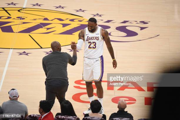 LeBron James of the Los Angeles Lakers high fives NBA Legend Kobe Bryant during a game between the Los Angeles Lakers and Atlanta Hawks on November...