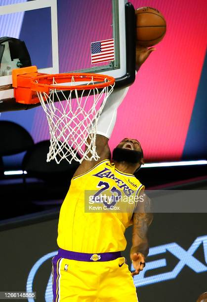 LeBron James of the Los Angeles Lakers hits the ball against the backboard to save it from going out of bounds against the Sacramento Kings during...