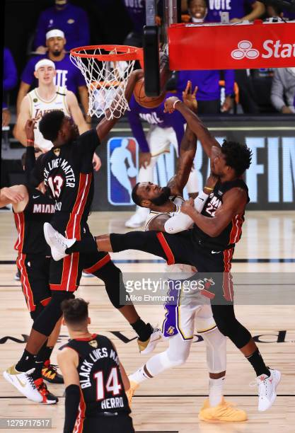 LeBron James of the Los Angeles Lakers is defended by Jimmy Butler of the Miami Heat and Bam Adebayo of the Miami Heat during the second quarter in...