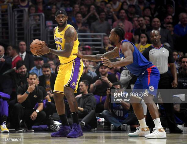 LeBron James of the Los Angeles Lakers is defended by Kawhi Leonard of the LA Clippers during the first half in the LA Clippers season home opener at...