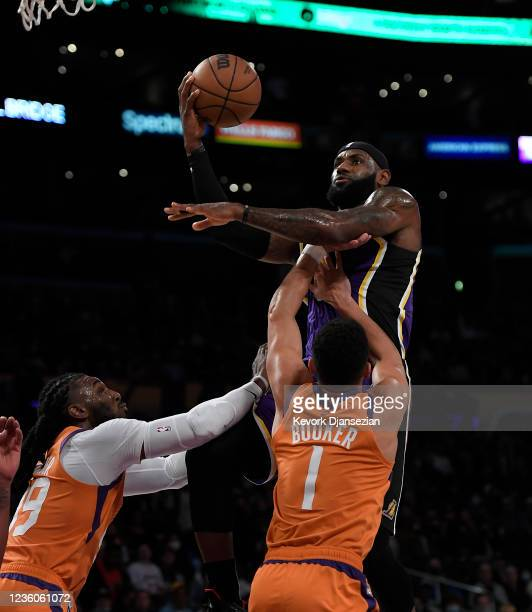 LeBron James of the Los Angeles Lakers is fouled by Devin Booker of the Phoenix Suns with Jae Crowder defending during the first half of the game at...
