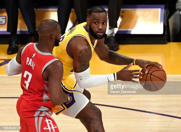LeBron James of the Los Angeles Lakers is guarded by Chris Paul of the Houston Rockets as he makes his home debut at Staples Center on October 20...