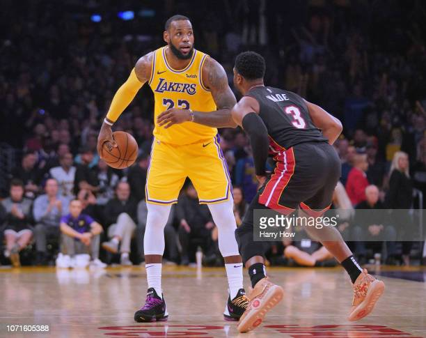 LeBron James of the Los Angeles Lakers is guarded by Dwyane Wade of the Miami Heat in Wade's last regular season game at Staples Center during a...