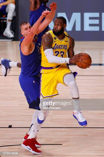 LeBron James of the Los Angeles Lakers is pressured by Nikola Jokic of the Denver Nuggets during the third quarter in Game One of the Western...