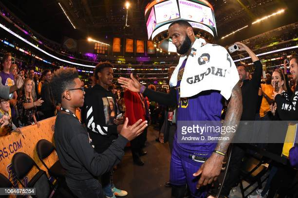LeBron James of the Los Angeles Lakers is seen shaking hands with his sons Bryce Maximus James and LeBron James Jr after winning the game against the...