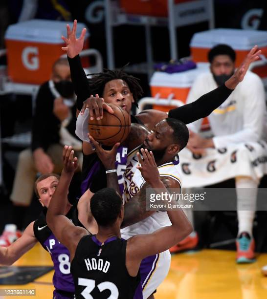 LeBron James of the Los Angeles Lakers is surrounded by Malachi Flynn Rodney Hood and Freddie Gillespie of the Toronto Raptors during the first half...