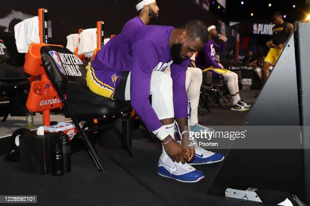LeBron James of the Los Angeles Lakers laces up after halftime against the Denver Nuggets in Game one of the Western Conference Finals of the 2020...