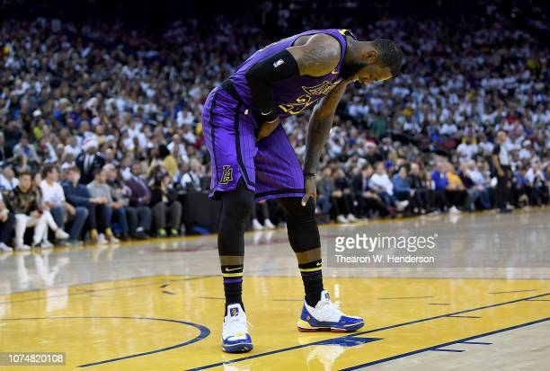 LeBron James of the Los Angeles Lakers leans over in pain after he was hurt against the Golden State Warriors during the second half of their NBA...