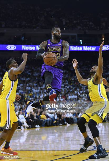 LeBron James of the Los Angeles Lakers leaps in the air to pass the ball between Kevon Looney and Andre Iguodala of the Golden State Warriors during...