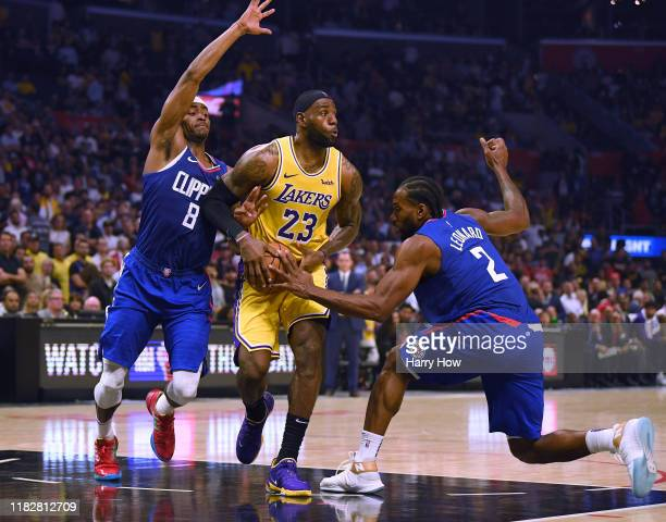 LeBron James of the Los Angeles Lakers looks to pass as Maurice Harkless and Kawhi Leonard of the LA Clippers defend during a 112-102 Clipper win in...