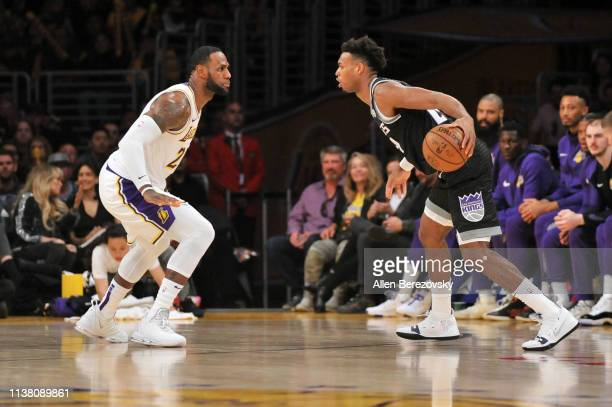 LeBron James of the Los Angeles Lakers plays defense against Buddy Hield of the Sacramento Kings at Staples Center on March 24 2019 in Los Angeles...