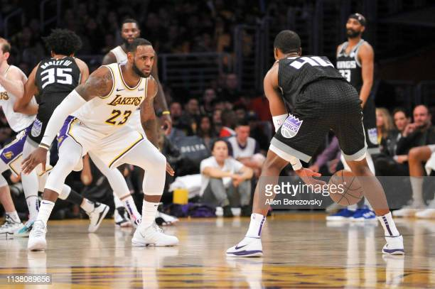 LeBron James of the Los Angeles Lakers plays defense against Harrison Barnes of the Sacramento Kings at Staples Center on March 24 2019 in Los...