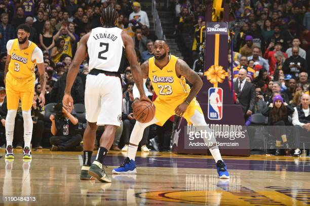 LeBron James of the Los Angeles Lakers plays defense against Kawhi Leonard of the LA Clippers during the game on December 25 2019 at STAPLES Center...