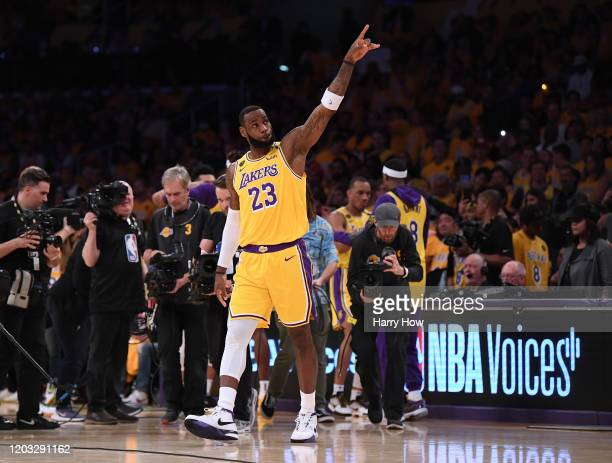 LeBron James of the Los Angeles Lakers points at the two retired jerseys in the rafters to honor Kobe Bryant before the game against the Portland...