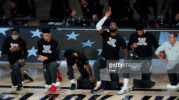 LeBron James of the Los Angeles Lakers points upwards while kneeling with teammates prior to facing the Denver Nuggets in the first half at The Arena...
