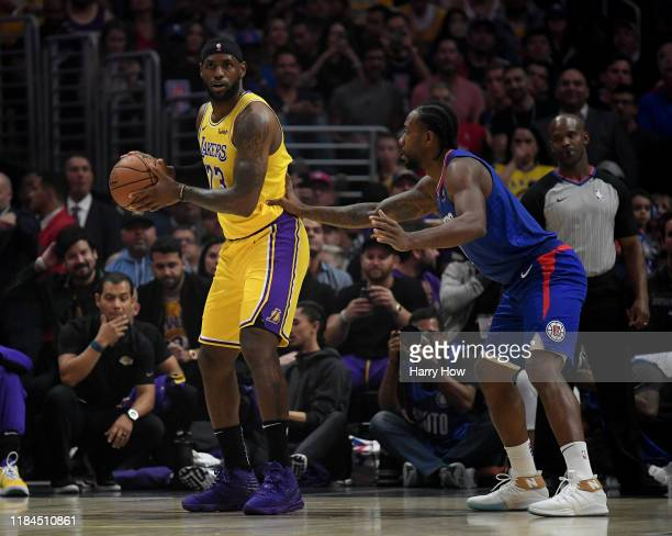 LeBron James of the Los Angeles Lakers post up Kawhi Leonard of the LA Clippers during the LA Clippers season home opener at Staples Center on...