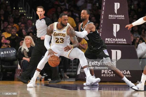 LeBron James of the Los Angeles Lakers posts up Harrison Barnes of the Sacramento Kings at Staples Center on March 24 2019 in Los Angeles California...
