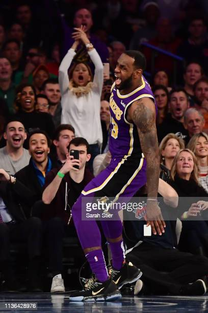 LeBron James of the Los Angeles Lakers reacts after making a slam dunk during the second half of the game against the New York Knicks at Madison...