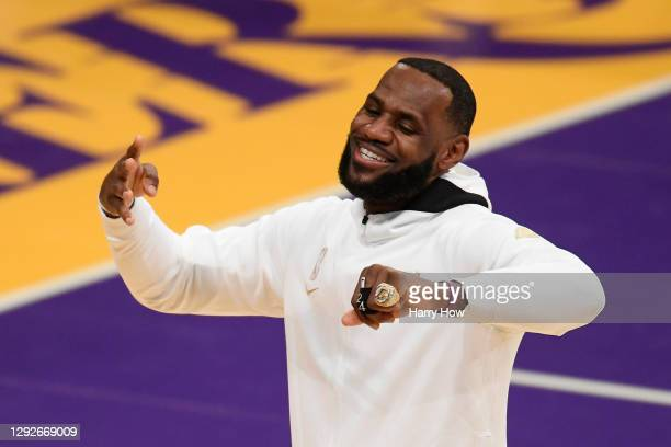 LeBron James of the Los Angeles Lakers reacts after receiving his 2020 NBA championship ring during a ceremony before the opening night game against...