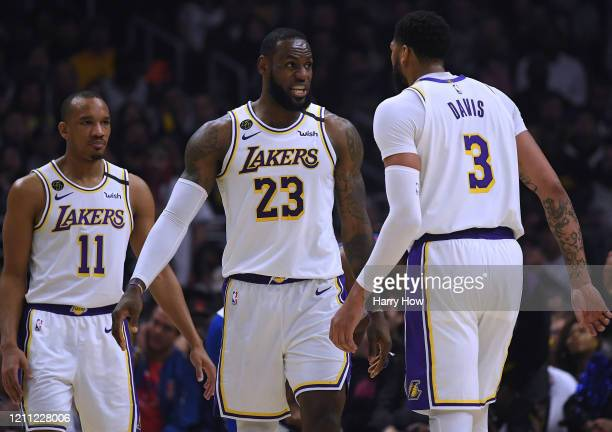 LeBron James of the Los Angeles Lakers reacts between Avery Bradley and Anthony Davis during a 112103 win over the LA Clippers at Staples Center on...