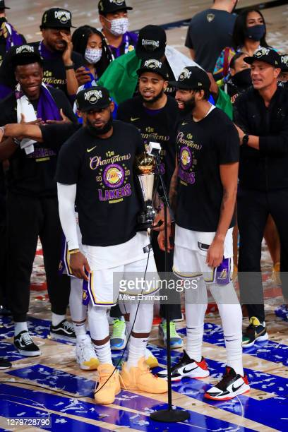 LeBron James of the Los Angeles Lakers reacts with Anthony Davis of the Los Angeles Lakers and the trophy after winning the 2020 NBA Championship...