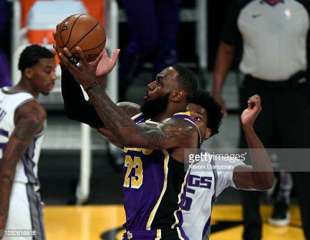 LeBron James of the Los Angeles Lakers scores a basket against Damian Jones of the Sacramento Kings and gets fouled during the first half at Staples...