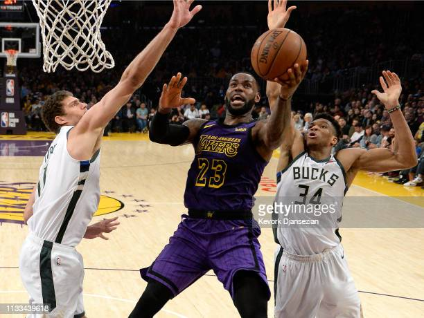 LeBron James of the Los Angeles Lakers scores a basket as he drives in between Giannis Antetokounmpo and Brook Lopez of the Milwaukee Bucks during...