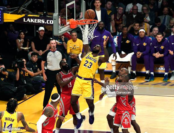 LeBron James of the Los Angeles Lakers scores a basket as James Harden Chris Paul Carmelo Anthony and PJ Tucker of the Houston Rockets look on as...