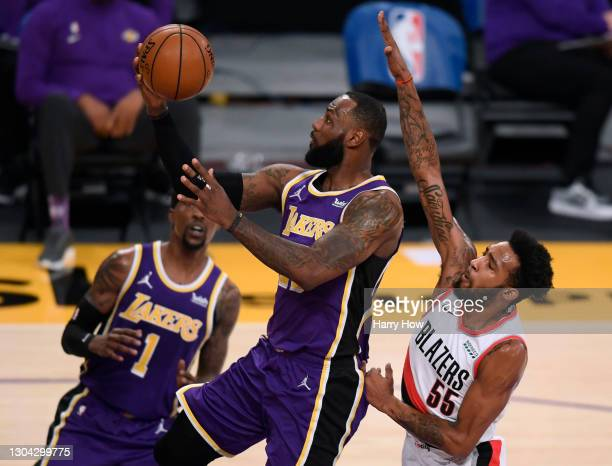 LeBron James of the Los Angeles Lakers scores on a layup past Derrick Jones Jr. #55 of the Portland Trail Blazers during the first quarter at Staples...