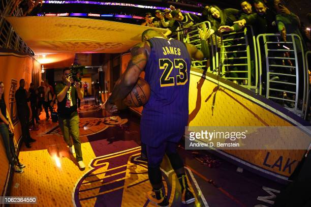 LeBron James of the Los Angeles Lakers shakes hands with fans as he walks off the court after the game against the Portland Trail Blazers on November...