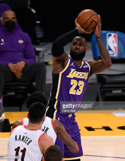 LeBron James of the Los Angeles Lakers shoots a jumper over Derrick Jones Jr. #55 and Enes Kanter of the Portland Trail Blazers during the first...