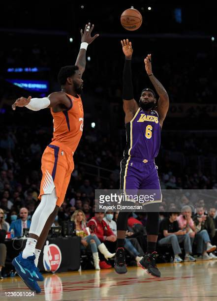 LeBron James of the Los Angeles Lakers shoots a three point basket as he is defended by Deandre Ayton of the Phoenix Suns during the first half of...