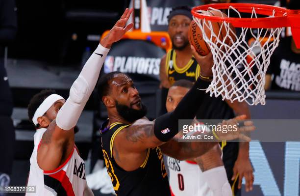 LeBron James of the Los Angeles Lakers shoots against Carmelo Anthony of the Portland Trail Blazers during the second quarter in Game Four of the...