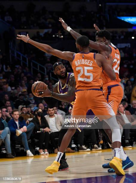 LeBron James of the Los Angeles Lakers shoots is defended by Deandre Ayton and Mikal Bridges of the Phoenix Suns during the first half of the game at...