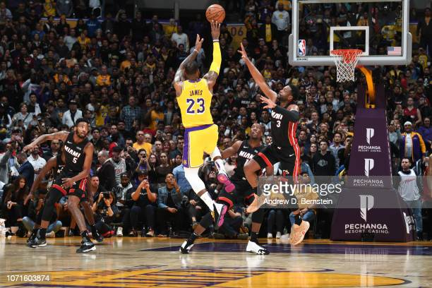 LeBron James of the Los Angeles Lakers shoots the ball against Dwyane Wade of the Miami Heat on December 10 2018 at STAPLES Center in Los Angeles...