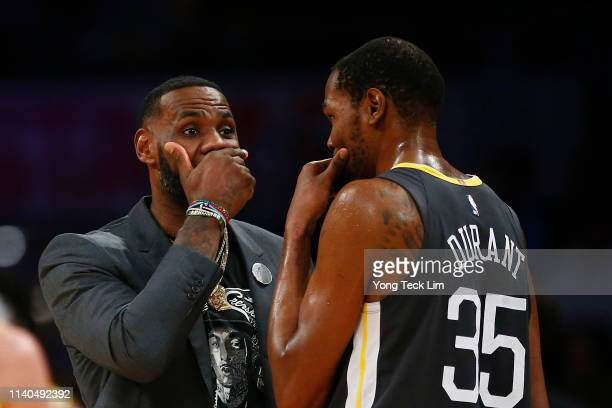 LeBron James of the Los Angeles Lakers speaks to Kevin Durant of the Golden State Warriors during a timeout in the first half at Staples Center on...