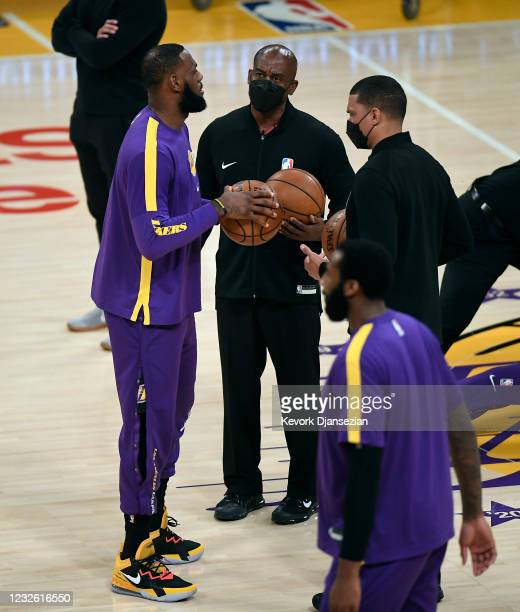 LeBron James of the Los Angeles Lakers talks to the referees as he checks the basketballs during pre-game warm-ups before the start of a basketball...