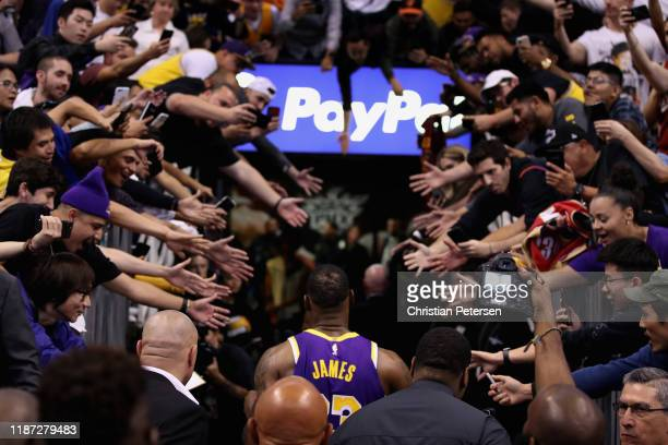 LeBron James of the Los Angeles Lakers walks off the court past fans following the NBA game against the Phoenix Suns at Talking Stick Resort Arena on...