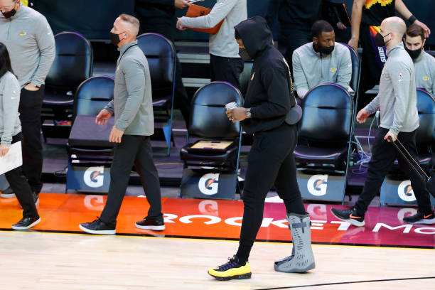 LeBron James of the Los Angeles Lakers walks to the locker room during half-time to the NBA game against the Phoenix Suns at Phoenix Suns Arena on...