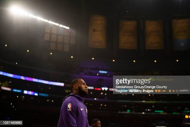 LeBron James of the Los Angeles Lakers warms up under the Championship banners and retired jerseys in the rafters of Staples Center before the...