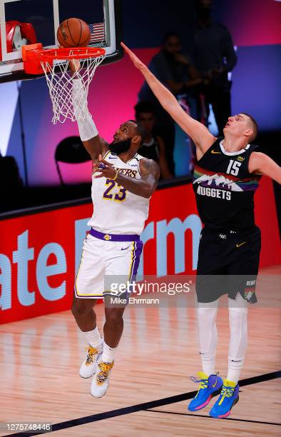 LeBron James of the Los Angeles Lakers with a lay-up as Nikola Jokic of the Denver Nuggets defends during the fourth quarter in Game Three of the...