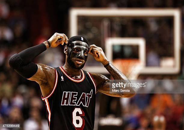 LeBron James of the Miami Heat adjusts a protective mask to begin the game against the New York Knicks at AmericanAirlines Arena on February 27 2014...