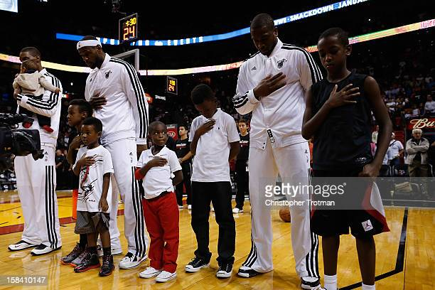 LeBron James of the Miami Heat and Dwyane Wade of the Miami Heat stand with their sons during the national anthem prior to the game against the...