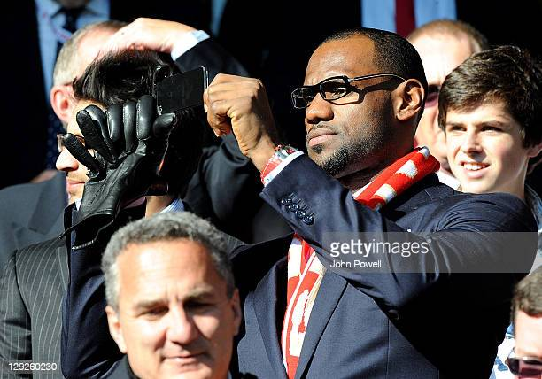 LeBron James of the Miami Heat and minority shareholder of Liverpool football club uses his mobile phone during the Barclays Premier League match...