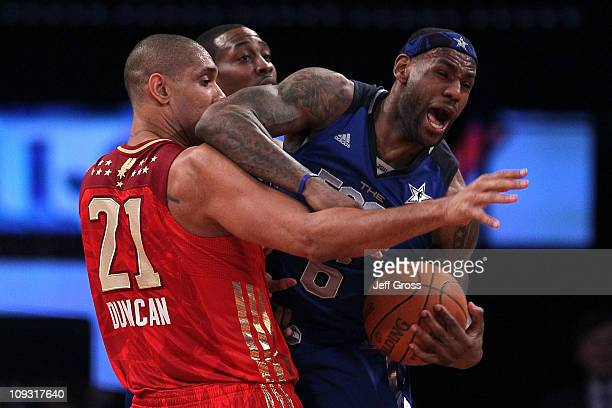 LeBron James of the Miami Heat and the Eastern Conference reacts as he is guarded by Tim Duncan of the San Antonio Spurs and the Western Conference...