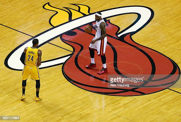 LeBron James of the Miami Heat brings the ball up the floor against the Paul George of the Indiana Pacers during Game Three of the Eastern Conference...