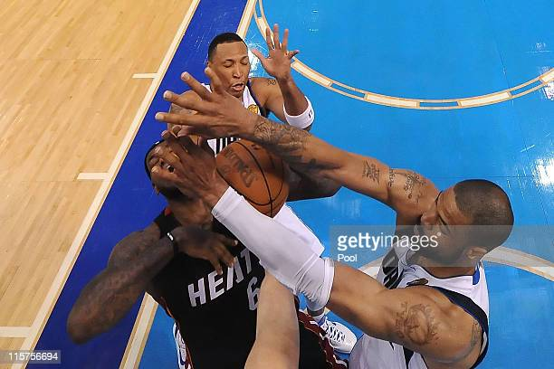 LeBron James of the Miami Heat draws contact from Tyson Chandler and Shawn Marion of the Dallas Mavericks in the second half of Game Five of the 2011...