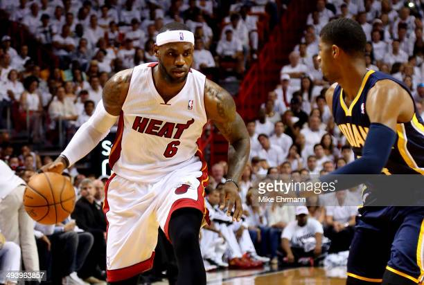 LeBron James of the Miami Heat dribbles the ball as Paul George of the Indiana Pacers defends during Game Four of the Eastern Conference Finals of...